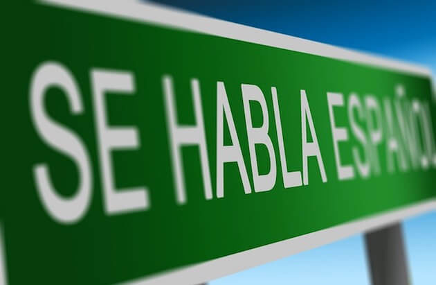 "A green sign with the words ""se habla español"" in white."