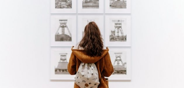 A person looking at a selection of artwork in a gallery.